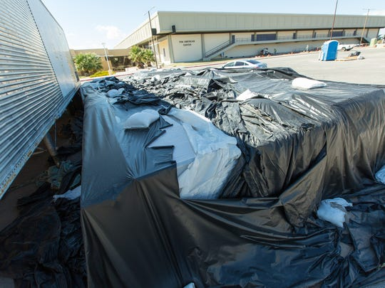 Parquet basketball flooring used in the Pan American Center at New Mexico State University from 1988 to 2012 is underneath tarps on the east side of the Pan Am on Monday, October, 10 2016, and is up for auction at www. publicsurplus.com. Currently one bid of $1000 has been placed on the item, but the reserve has not yet been met.