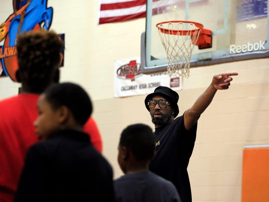 Jaborri Thomas, right, leads children in basketball drills during the J.T. and Friends Youth Sports Camp at Callaway High School Tuesday.