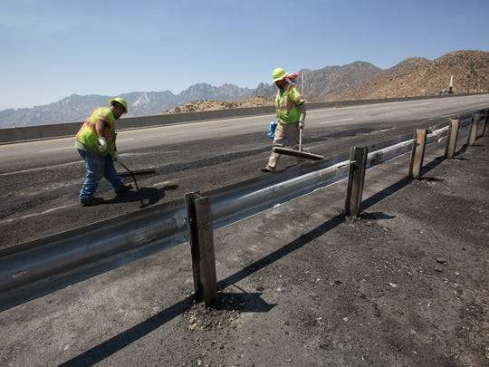 Randy Medina, left, and Hugo Quezada, right, with New Mexico Department of Transportation, work Monday June 25, 2018, to put a temporary patch over potholes formed after a vehicle burned on the side of Highway 70 on Sunday night.