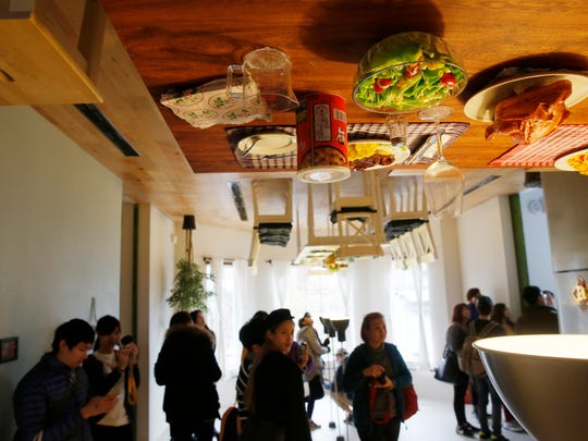 Visitors look around inside an upside-down house created