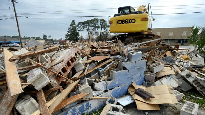 The Hip Pocket Deli is torn down by workers for Cross Environmental Services, Inc., a contractor for the Florida Department of Transportation, on Tuesday as the state acquires the property through eminent domain for a future road project. The family owned restaurant was popular among those in the military and was open for over 22 years.