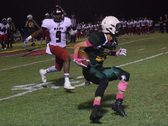 Menard's Adam Brown (21, right) gets past Many defenders including Isaiah Smith (9, left) to gain a first down in Week 7.