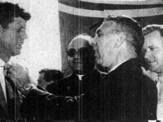 Kennedy arrives at parish airport, where he was  presented with the  Yambilee tie (taken from John Thistlethwaite's neck) .