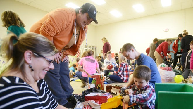 Teacher Sommer Vansickle, left, and Mid-East Career and Technology Students Mitchell Darr and Kyle Hrinko watch Starlight School student Terry McWhorter, 4, open Christmas presents at the two schools annual Adopt-a-Child party on Friday.