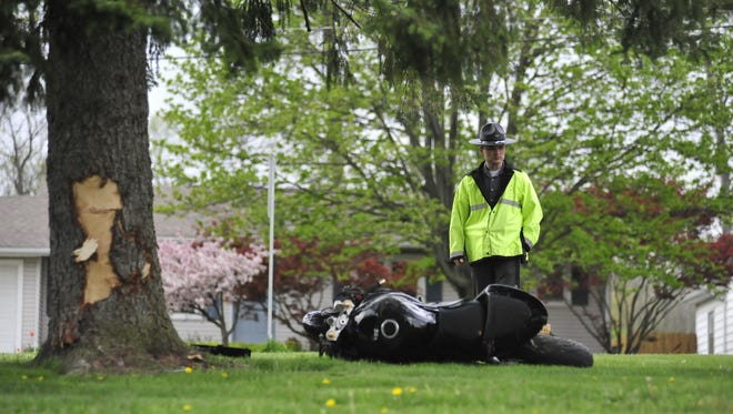 Sgt. Aaron Williams of the Ohio Highway Patrol examines debris from a motorcycle crash Wednesday evening.