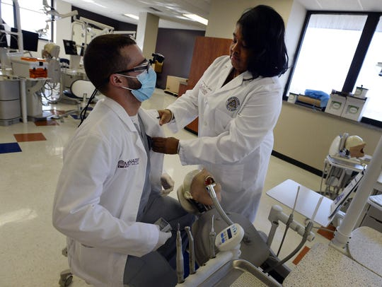 Meharry's School of Dentistry Dean, Dr. Cherae Farmer-Dixon, adjusts student David Gonzalez's coat before beginning a dental clinical lab class on Tuesday, March 6, 2018, in Nashville Tenn.