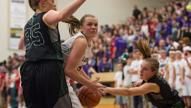 Delsie Johnson of Fort Collins tries to find a path through Fossil Ridge defenders Reilly Dunn and Ashley Steffeck during a game Tuesday, January 31, 2017. The SaberCats defeated the Lambkins 41-38.