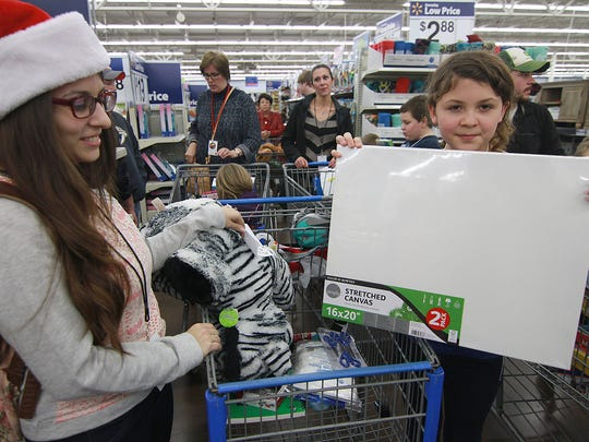 Nine-year-old Alexia McCandeless is an artist in need of a canvas as she shops with Mysteree McDaniel at Christmas 4 Kids at Walmart in Hendersonville on Dec. 15, 2015.