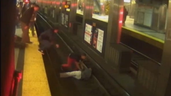 Bystanders rescue a man who fell off the platform and onto the Boston T tracks.