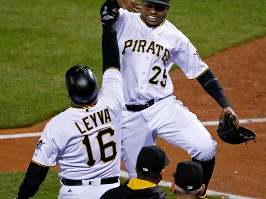 Pittsburgh Pirates' Gregory Polanco (25) celebrates the team's 4-1 win over the Cincinnati Reds with coach Nick Leyva (16) at the end of a baseball game in Pittsburgh, Friday, April 29, 2016. (AP Photo/Gene J. Puskar)