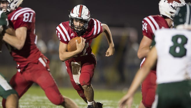 New Palestine High School junior Zach Neligh (11) rushes the ball into the Pendleton Heights defense during the second half of an IHSAA high school football game at New Palestine High School, Friday, September 15, 2017. New Palestine won 41-21.