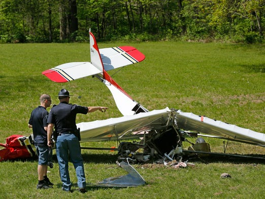 Jarid Larson, left., of Attica Police Department, and Trooper Sean Swaim of Indiana State Police prepare to photograph the scene after a plane crash Saturday, May 10, 2014, off East Covered Bridge Road about three miles south of Attica. According to Trooper Swaim, an ultra-light experimental plane crashed around 1:30 in the area known as Rob Roy. The pilot of the plane, Charles Coffing, 72, of Covington, was killed in the accident.