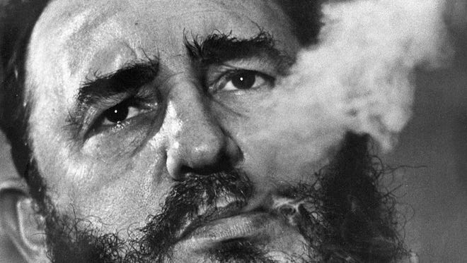 Fidel Castro exhales cigar smoke during a March 1985 interview at his presidential palace in Havana.