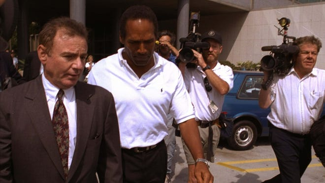 Former NFL star O.J. Simpson, center, and his attorney Howard Weitzman, right, are besieged by the media as they leave police headquarters in downtown Los Angeles Monday, June 13, 1994, after Simpson was questioned in connection with the apparent murders of his ex-wife Nicole Brown Simpson and Ronald Lyle Goldman, 26, at the woman's Los Angeles condominium. (AP Photo/ Michael Caulfield)