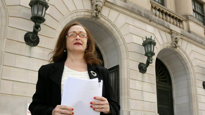 Rita Sklar, executive director of the American Civil Liberties Union of Arkansas carries a copy of a lawsuit  challenging Arkansas' voter ID law before a news conference in front of the Pulaski County Court House in Little Rock, Ark., Wednesday, April 16, 2014. The group on behalf of four voters seeks to block a new state law requiring voters to show photo identification at the polls before it is enforced for the first time state-wide in the primary election next month. (AP Photo/Danny Johnston)