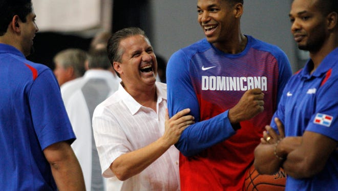 University of Kentucky head coach John Calipari jokes with members of the Dominican Republic national team before the teams' exhibition game in Nassau, Bahamas. August 15, 2014.