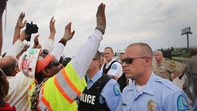 Police block demonstrators protesting the killing of Michael Brown from gaining access to Interstate 70 on Sept.  10, 2014, near Ferguson, Mo.