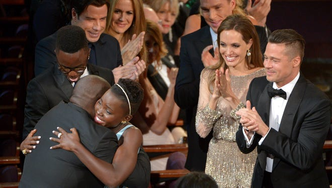 """Director Steve McQueen, left, congratulates Lupita Nyong'o on her win for best actress in a supporting role for """"12 Years a Slave"""" as her brother Peter, background from left, and actors John Travolta, Kelly Preston, Benedict Cumberbatch, Angelina Jolie and Brad Pitt, look on, during the Oscars at the Dolby Theatre on Sunday, March 2, 2014, in Los Angeles.  (Photo by John Shearer/Invision/AP) ORG XMIT: CACJ412"""