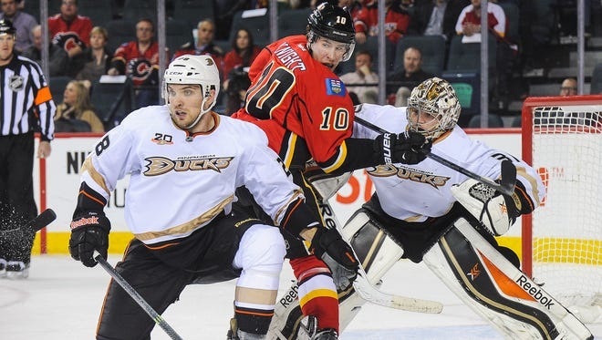 Corban Knight #10 of the Calgary Flames looks for an opportunity as Mark Fistric #28 (L) and Frederik Andersen #31 of the Anaheim Ducks defend during an NHL game at Scotiabank Saddledome.