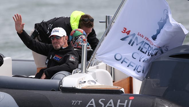 Oracle CEO Larry Ellison waves from a boat before the start of race one of the Louis Vuitton Cup finals on Aug. 17, 2013, in San Francisco.