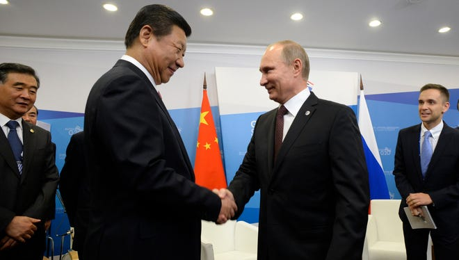 Chinese President Xi Jinping greets Russian President Vladimir Putin during a bilateral meeting in St. Petersburg this month.