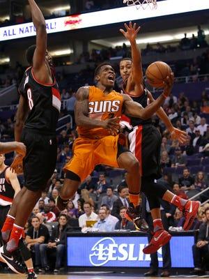 Phoenix Suns guard Eric Bledsoe, center, drives between Portland Trail Blazers forward Al-Farouq Aminu, left,  and guard C.J. McCollum, right, in the fourth quarter during an NBA basketball game, Friday, Dec. 11, 2015, in Phoenix.
