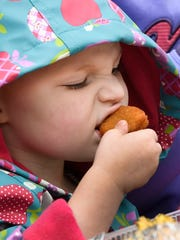 Gryffin Shaw, 3 years-old, munches on a chicken nuggett as she enjoys lunch at the Henderson Breakfast Lions Club Tri-Fest Friday, April 21, 2017.