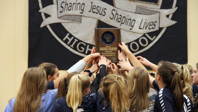 The Lake Country Lutheran volleyball team celebrates with a regional plaque after sweeping Kenosha Christian Life on Oct. 21.