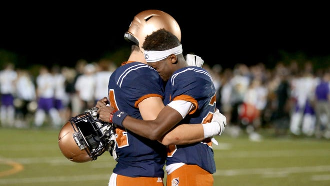 Cienega's Dylan Hoose (24) left, and Rodney Rodgers II (23) console one another as the Notre Dame Prep players and fans celebrate the Saints 37-34 win in the state 5A semifinal at Mountain View High School, Friday November 17, 2017, Tucson, Ariz.
