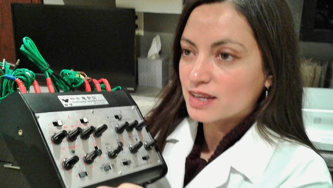 Dr. Ana Falk explains the equipment she uses for electro-stimulation of acupuncture needles in her practice at Animal Kingdom in North Liberty.