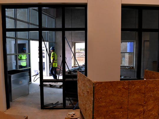 A construction worker exits through the main entrance to the Wylie East Elementary School Friday. The new school has been designed locally with modern security concerns in mind.