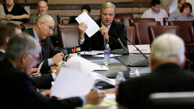 Joseph Walsh, center, Iowa Workforce Development's former chief administrative law judge, testifies during the Iowa Senate Government Oversight Committee meeting on Aug. 26 at the Iowa Capitol.