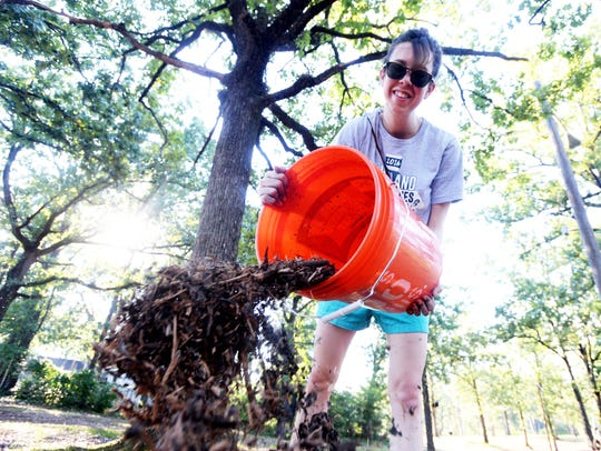 Volunteer Madison Poche helps lay down mulch with Re-Form