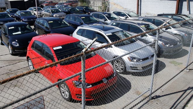 Volkswagen diesels are shown behind a security fence on a storage lot near a VW dealership Wed., Sept. 23, 2015, in Salt Lake City.