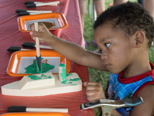 At Home Depot's tent, kids assemble crafts. Two-year-old Chase Johnson paints his boat.