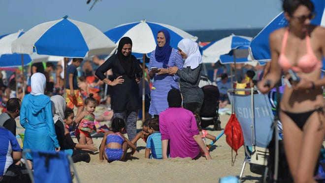 Amanny Khattab, center, wearing a burkini with her family at Point Pleasant Beach, N.J., on Sunday, Aug. 28, 2016.