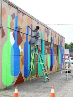Travis Baez, an assistant to Dover artist Jon Stucky, paints a mural on the north side of the Wine Rack building at 150 S. Broadway downtown New Philadelphia on Wednesday.