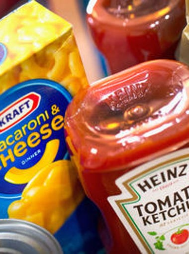 In this photo illustration, Kraft and Heinz products are shown on March 25, 2015 in Chicago. The two companies merged to form the third largest food and beverage company in North America, and now says it is cutting about 2,500 jobs as part of its plan to slash costs.