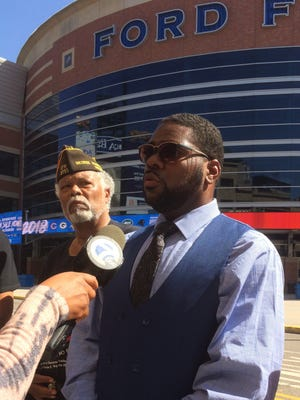 Rev. Charles Williams II, president of the National Action Network's Michigan Chapter, front, addresses reporters outside of Ford Field on May 25, 2018.