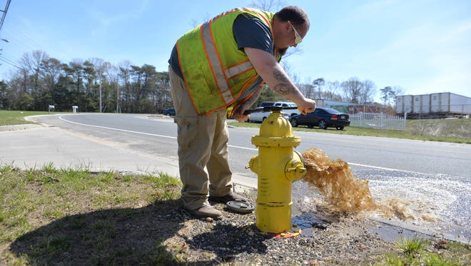 Millville water utility worker Adam Seitz tests a fire hydrant on Bogden Boulevard as testing of all the city's hydrants is completed, Monday, Apr. 18, 2016 in Millville.
