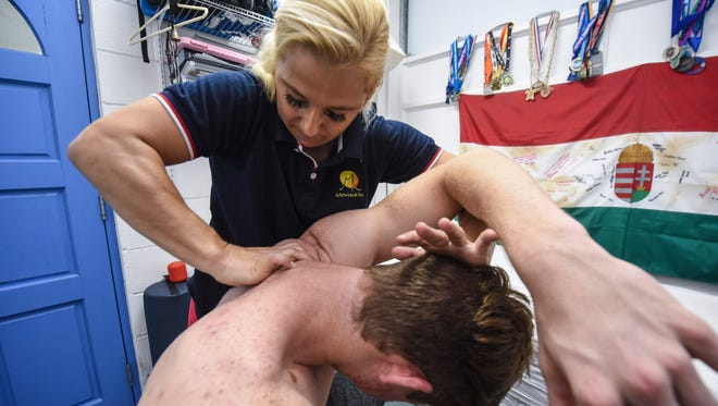 Sports Therapist Adrienn Balazs Cogger uses Active Release Technique therapy to increase arm and shoulder mobility and reduce back pain for CrossFit athlete Ethan Elwell, 17, while at Custom Fitness in Anigua on Wednesday, June 27, 2018. Elwell plans to compete in the World CrossFit Games scheduled to be held in Madison, Wisconsin on Aug. 1.