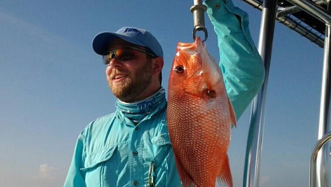 Pensacola resident Brett Tennant shows off a red snapper he caught in the Gulf of Mexico.