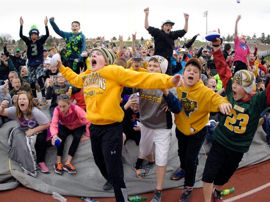 A crowd celebrates after watching the Philadelphia Eagles pick Bismarck native and former North Dakota State University quarterback Carson Wentz as the second pick in the first round of the NFL football draft on the scoreboard video screen at the Community Bowl in Bismarck, N.D., Thursday, April 28, 2016.   (Mike McCleary/The Bismarck Tribune via AP) MANDATORY CREDIT MBO