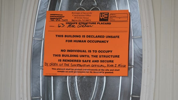 An unsafe building placard hangs on the front door
