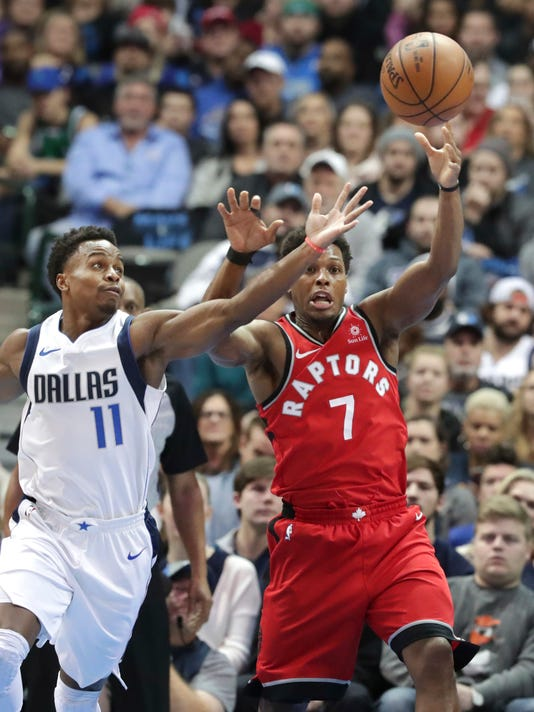 Toronto Raptors guard Kyle Lowry (7) and Dallas Mavericks guard Yogi Ferrell (11) reach for the ball during the first half of an NBA basketball game in Dallas, Tuesday, Dec. 26, 2017. (AP Photo/LM Otero)