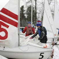 University of Vermont sailing team members Haley Brown, standing, and Lindsay Doyle return to a dock after a winter sailing practice on Lake Champlain in Burlington.