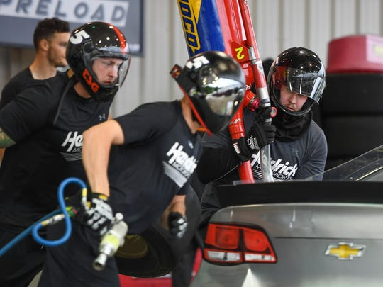 Former Clemson lineman Landon Walker, right, who is the gas man for NASCAR Sprint Cup series drive Kasey Kahne, practices with the crew at Hendrick Motor Sports this summer.