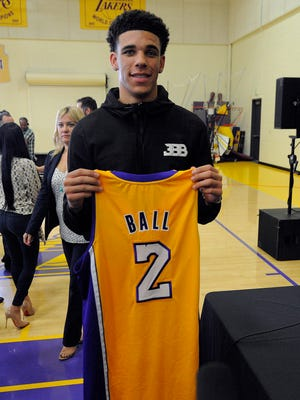Newly drafted Los Angeles Lakers player Lonzo Ball poses for photographs with his game jersey following introduction to media at Toyota Sports Center.
