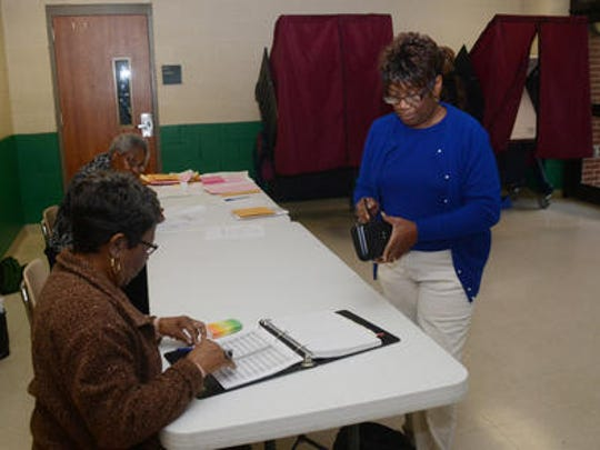 Poll commissioner Rose Franklin (left) looks for Carolyn Wilson's name in the book of voters at Precinct C7 at Peabody Magnet High School on Saturday as Wilson (right) prepared to vote in the House District 26 special election.