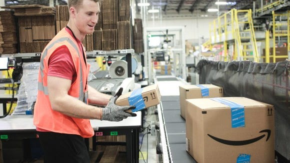 A male Amazon employee carrying a box to a conveyor belt at a fulfillment center